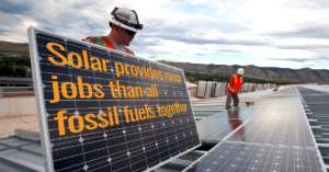A solar installer holding a panel that says solar creates more jobs than any other kind of energy